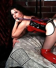 Male slave pleasing a Domme in shiny red PVC